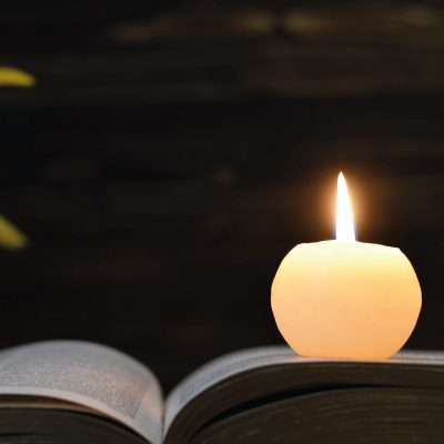 single candle lit placed on an open book