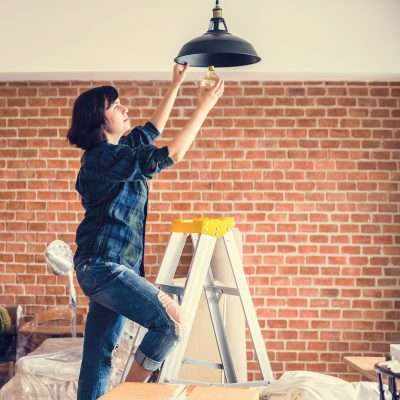 woman changing a light bulb on a ladder